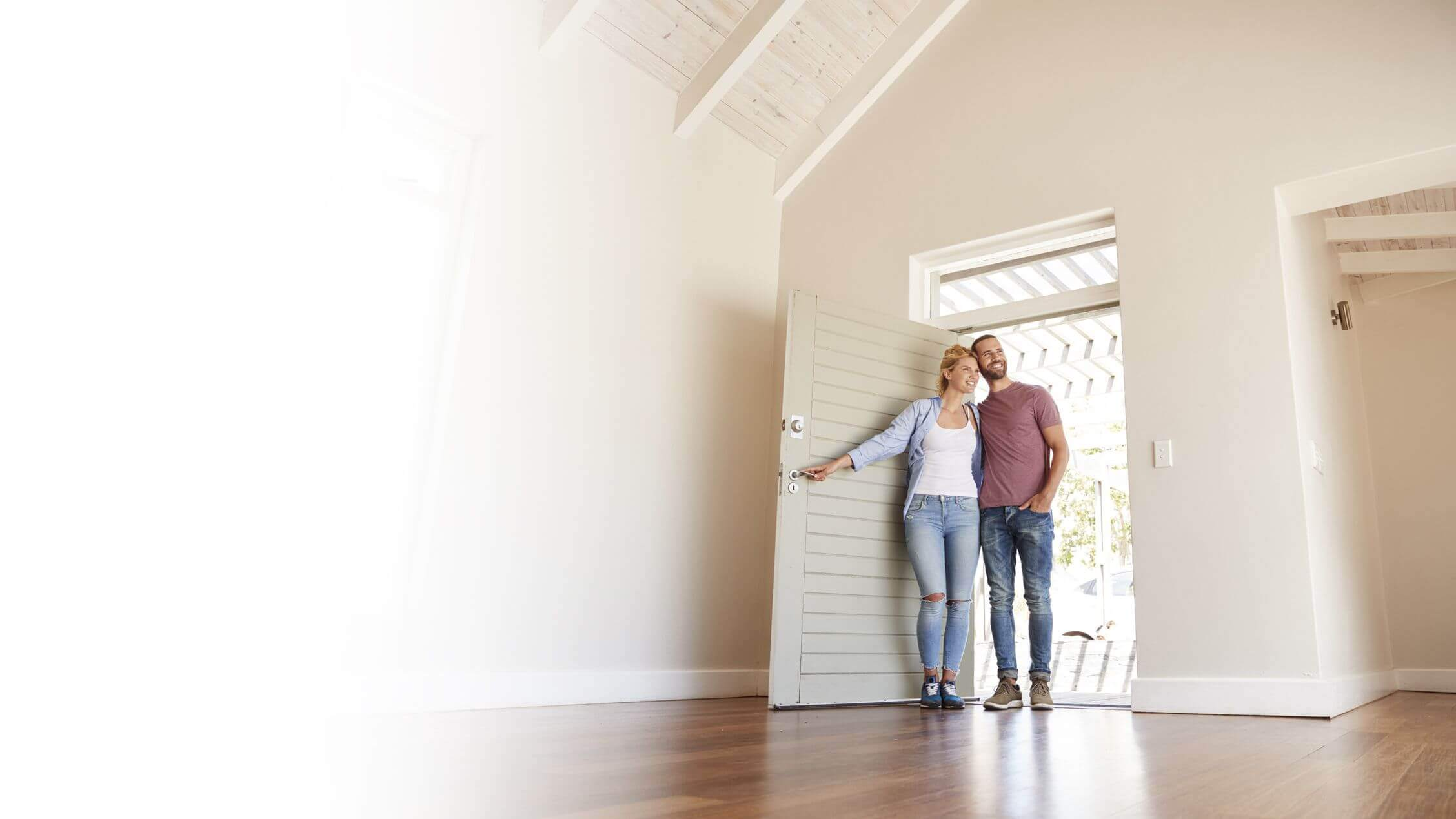 Banner image of couple at entry of home with lady opening the front door and couple smiling and looking inside